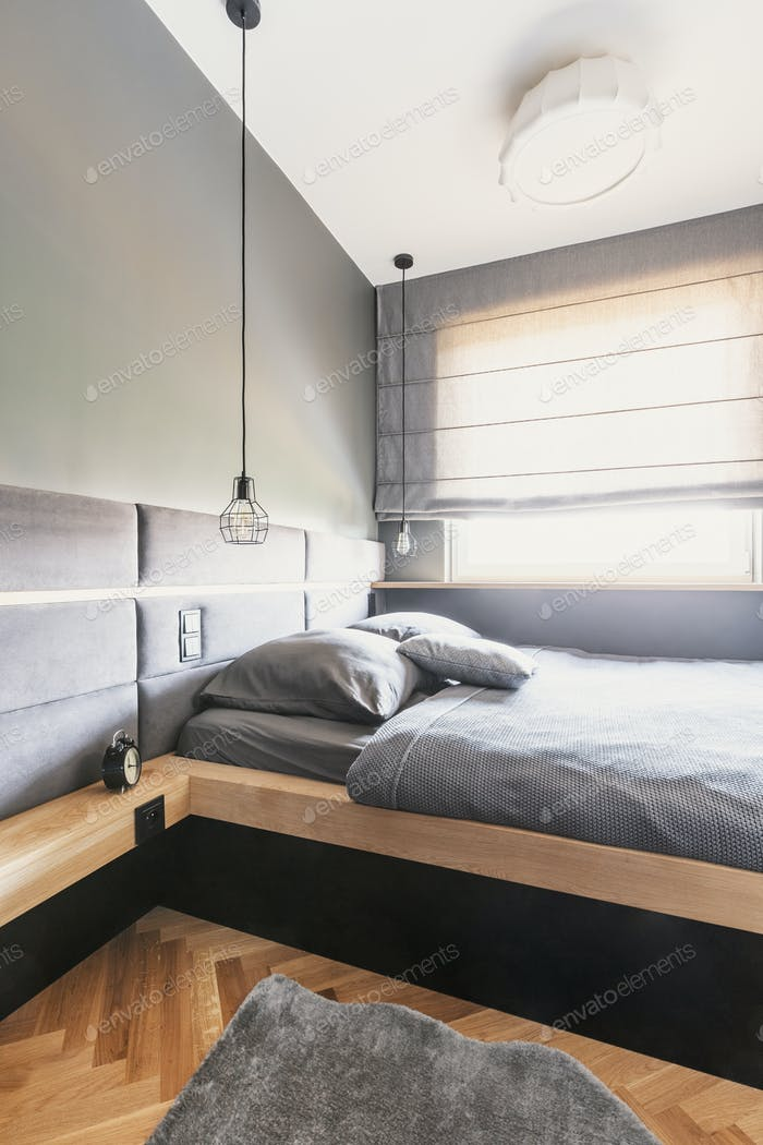 Grey sheets and cushions on wooden bed in minimal bedroom interi