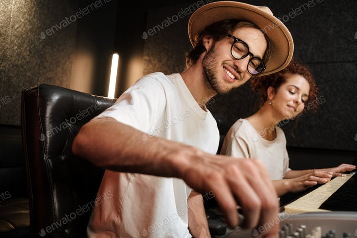 Young stylish people creating music in modern sound recording studio