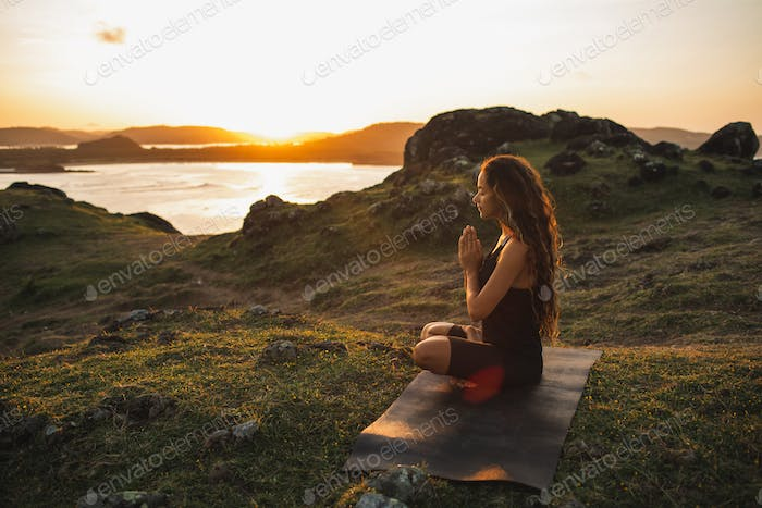 Woman doing yoga alone at sunrise with mountain and ocean view. Harmony with nature