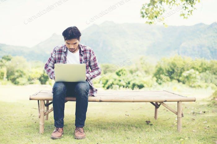 Junge Hipstermann arbeiten an einem sonnigen Tag am Computer im Park.