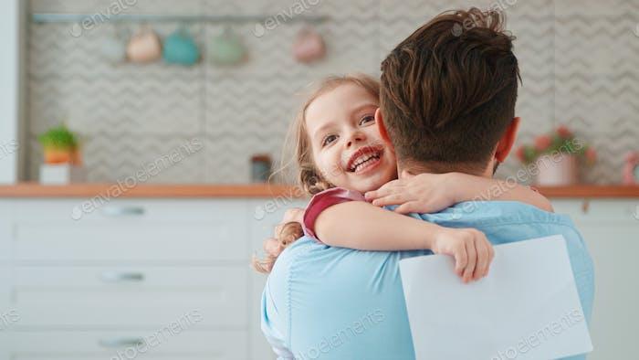 Linda niña abrazando a papá en la sala de estar