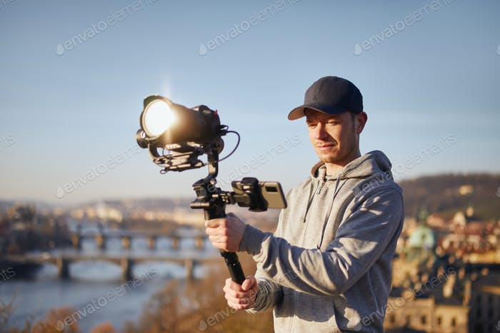 Man filming with camera and gimbal against urban skyline