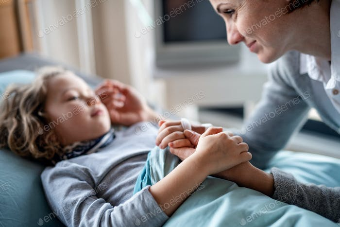 Caring mother visiting small girl daughter in bed in hospital.