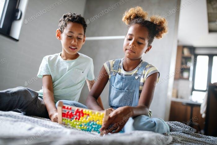 Children, education, plyaing happiness concept. Happy kids entertaining themselves at home