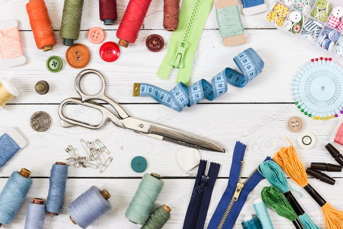 Tools and accessories for sewing on wooden background.