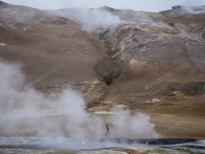 A person walks along the steamy edge of a hot spring.