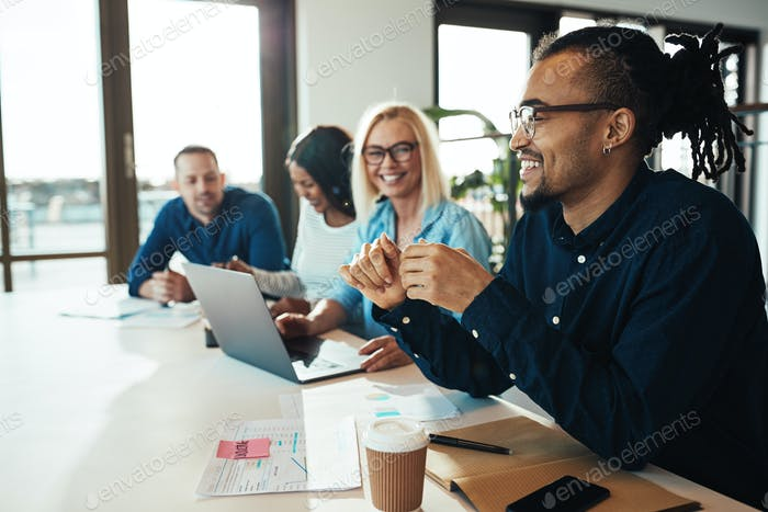Young African American businessman laughing during an office meeting