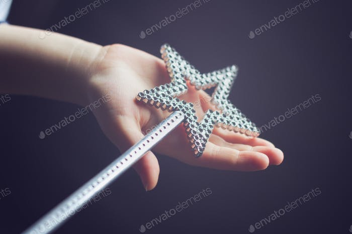 child hand holding a magic wand