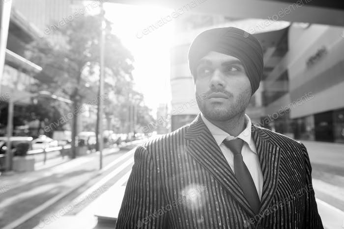 Young handsome Indian Sikh businessman wearing turban in the city outdoors