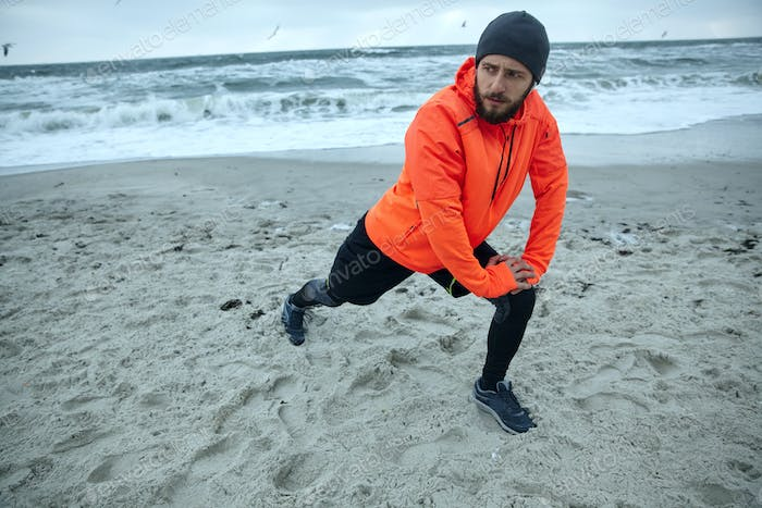brunette bearded runner stretching his muscles before running session