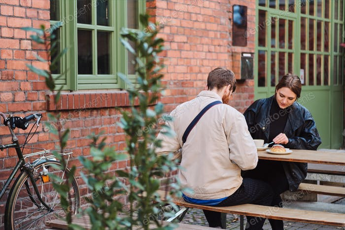 Young attractive couple resting together in street cafe