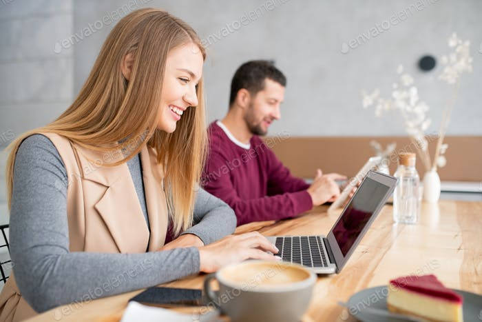 Cheerful girl looking at her friend while communicating through video-chat