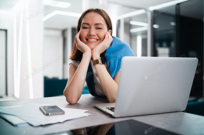 Happy smiling young woman sitting at desk with open laptop looking at camera. Successful smiling
