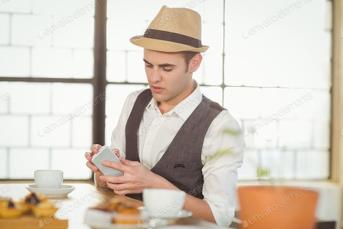 Concentrated hipster using smartphone at coffee shop