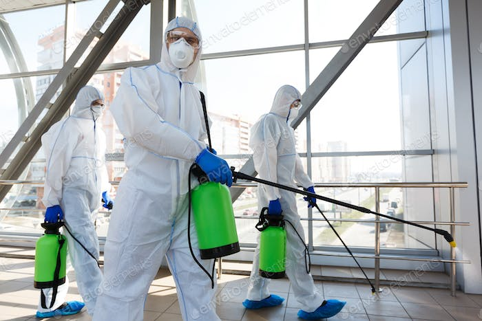 Professional workers in hazmat suits disinfecting indoor accommodation