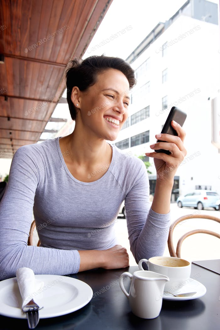 Smiling young woman looking at mobile phone at cafe