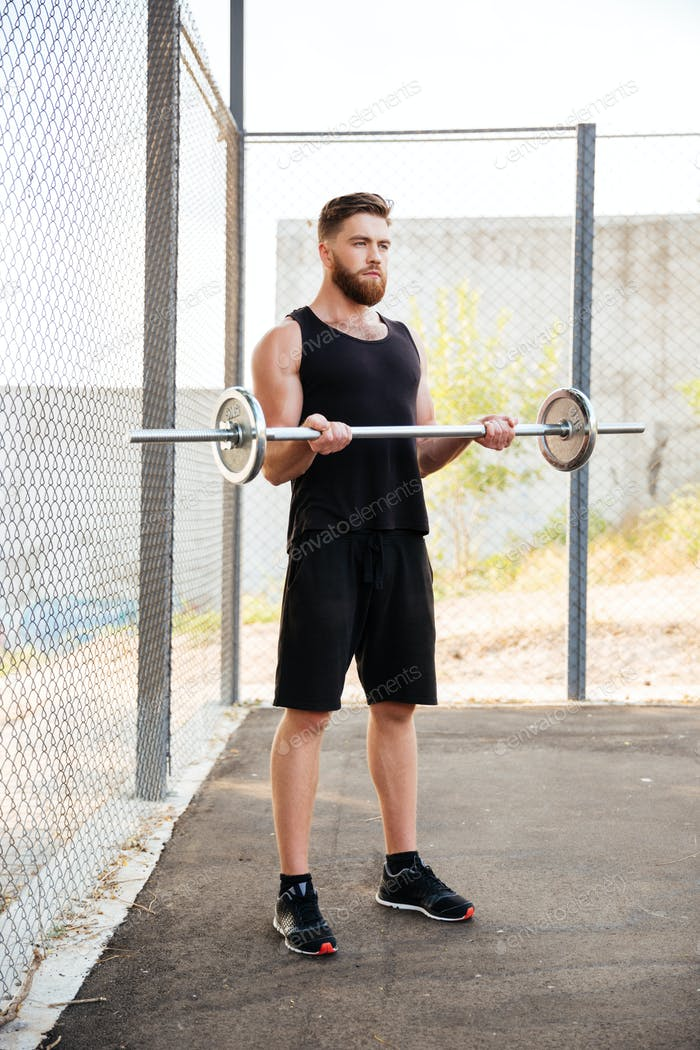 Full length of concentrated man athlete working out with barbell