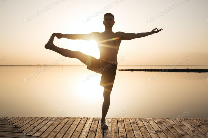 Concentrated young sportsman make yoga meditation exercises