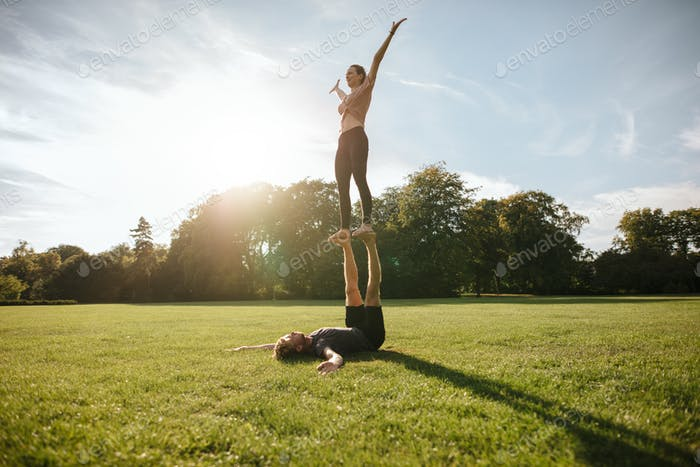 Couple doing acrobatic yoga exercise at park