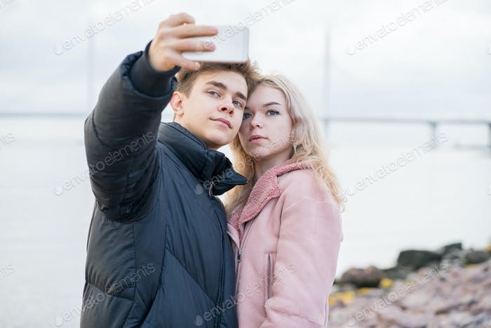 Teenage love concept. Cute brunette guy фтв young blonde girl