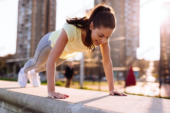 Picture of woman doing push ups in urban area