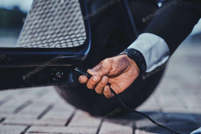 Der Mann lädt seinen neuen elektro- -Scooter