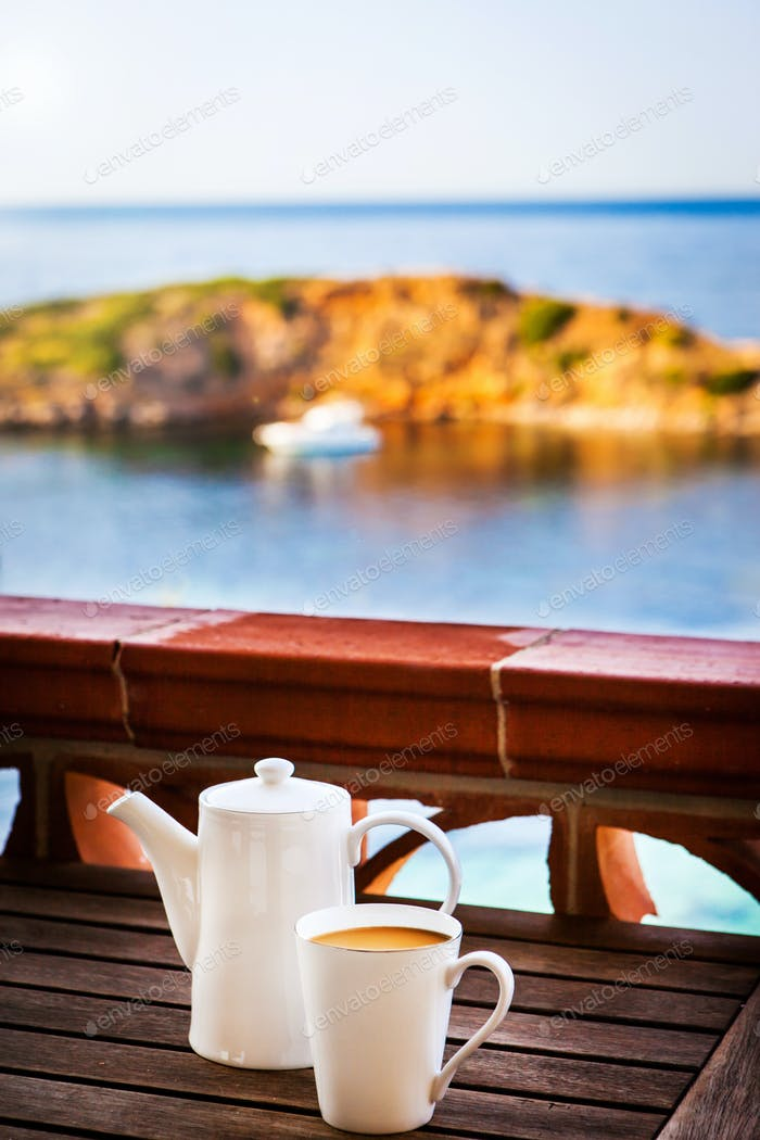 Cup of coffee and pot  on balcony with sea view background