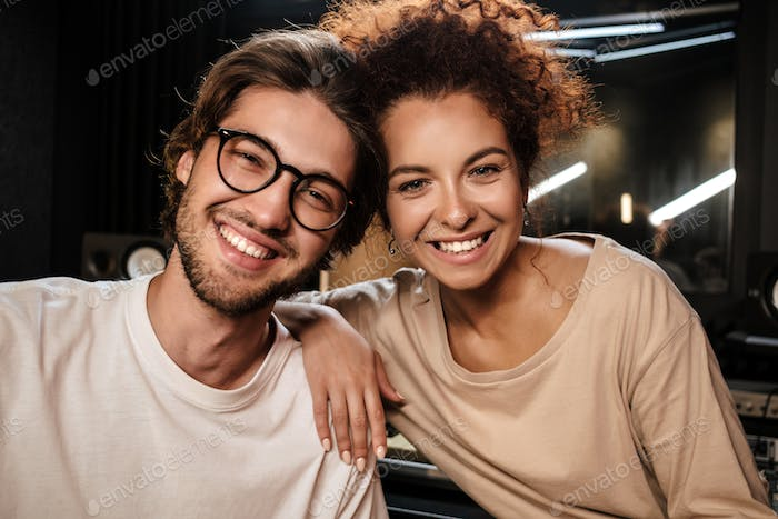 Portrait of young attractive musicians happily looking in camera in modern recording studio