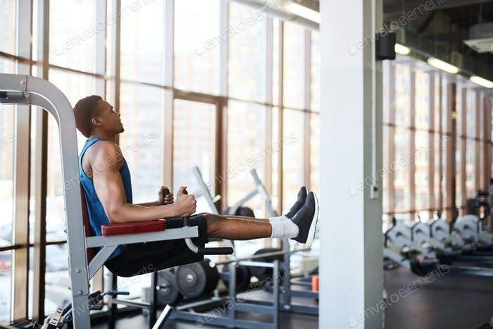 Muscular Man using Machines in Gym