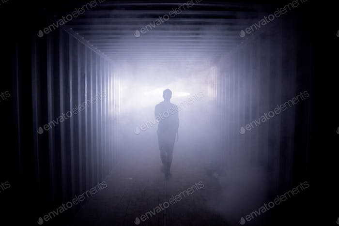 Silhouette of a man walking in a dark tunnel to the light, concept of death