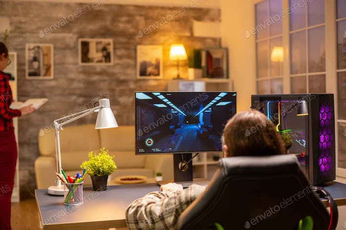 Back view of professional video gamer playing on powerful PC late at night in the living room