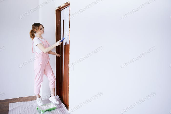 A girl in a pink work suit repaints an old door. Renovation and new life for old things.