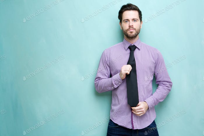 Young businessman holding necktie