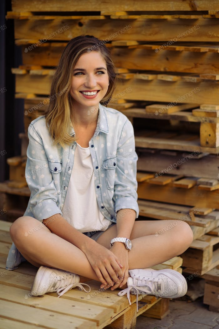 Charming girl sitting on a pallet