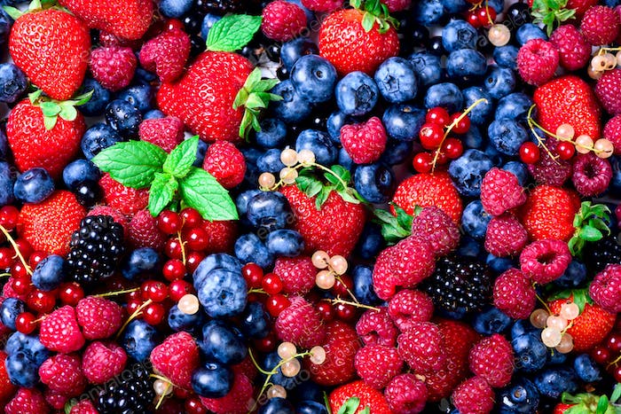 Macro colorful berries background. Top view. Summer food frame, border design. Assorted mix of