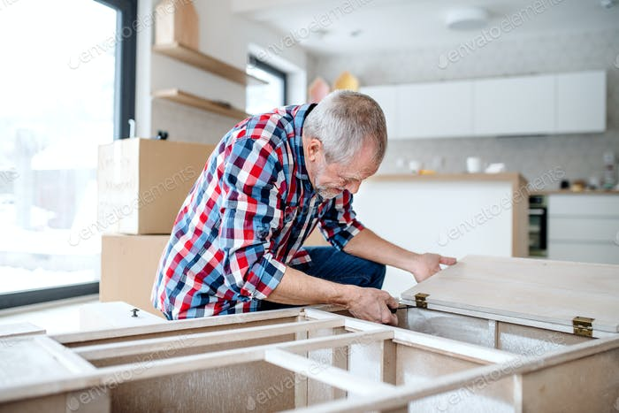 Senior man assembling furniture at home, a new home concept.