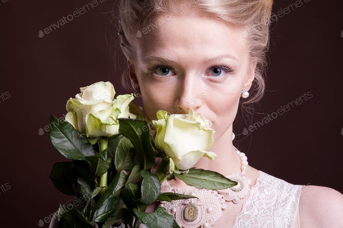 Blonde woman in victorian dress with roses in hands