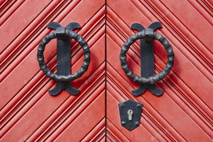 Antique metallic door knob on a red wooden doors. Horizontal