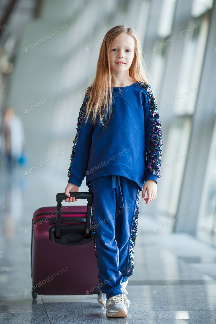 Adorable little girl in airport with her luggage
