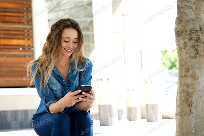 young woman sitting on bench looking at cellphone