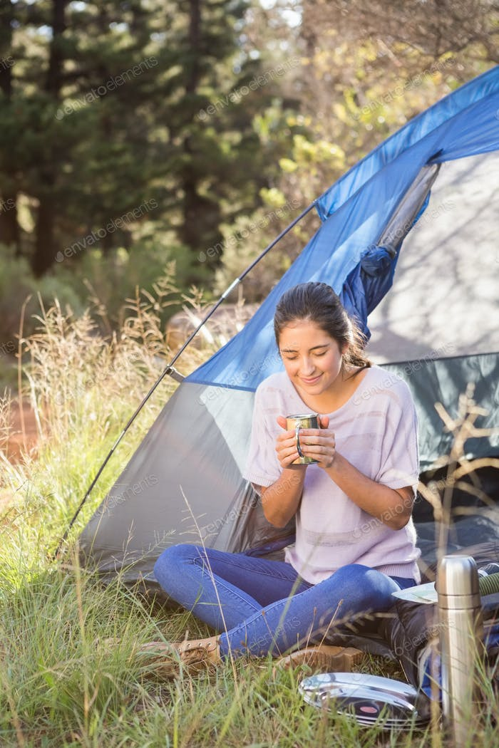 Brunette camper enjoying beverage and sitting in tent in the nature