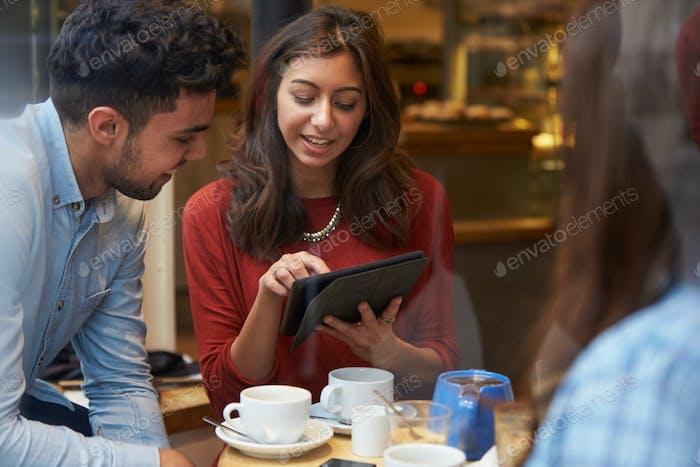 Gruppe von Freunden im Caf' mit digitalem Tablet