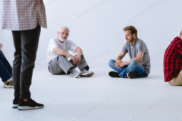 Man sitting on the floor in empty white room before psychotherapy