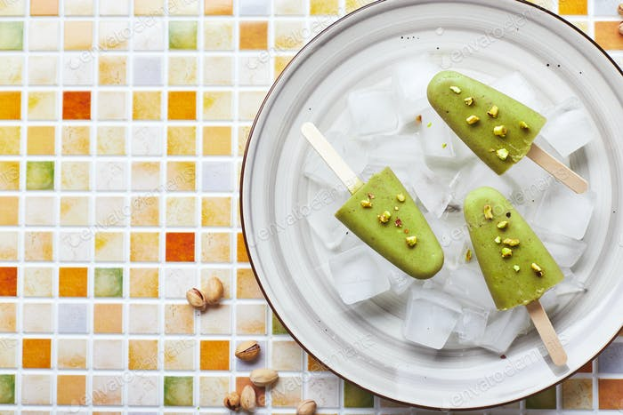 Frozen homemade pistachio popsicle in bowl of ice on mosaic tile table. Refreshing popsicle, frozen