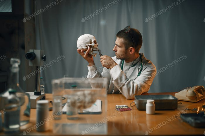 Psychiatrist in lab coat examines the human skull