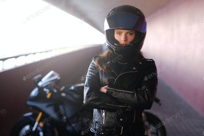 Attractive serious woman is standing next to her motobike crossing hands