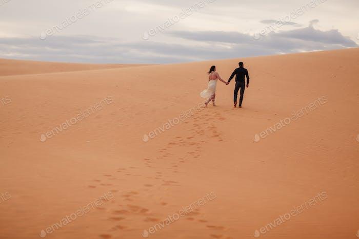 couple travel to arabian sand dune