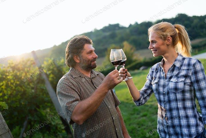 Bild von Menschen, die Rotwein im Weinberg verkosten