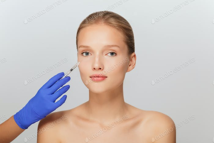 Portrait of young beautiful woman getting beauty injection in ey