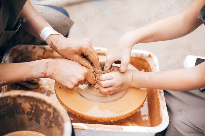 Hands of adult and child making pottery, working with wet clay closeup